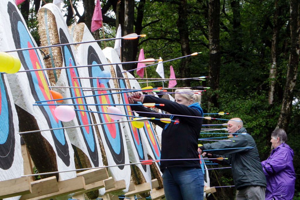 Archers pulling arrows from a line of targets filled with arrows